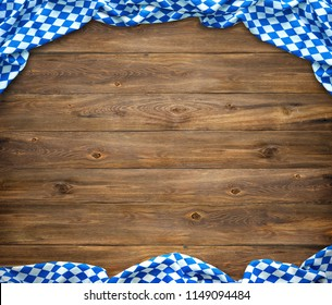 Rustic background for Oktoberfest with bavarian white and blue fabric on wooden table