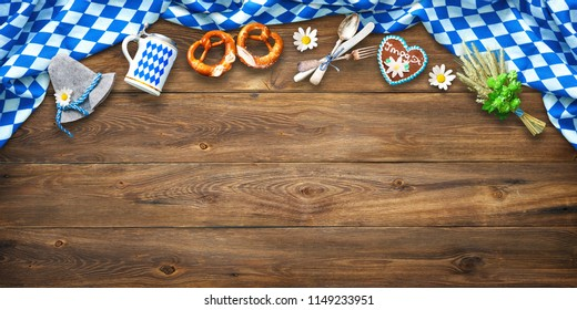 Rustic background for Oktoberfest with white and blue fabric, Bavarian hat, hop, beer stein, pretzel and gingerbread with letters I Mog Di means I love you on wooden table