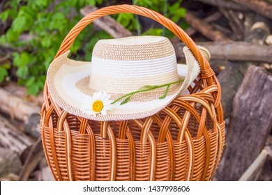 Rustic background. Wicker basket of rattan and straw sun hat on the background of old logs and firewood.