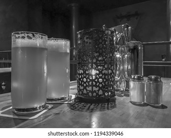 In a rustic bar, beer glasses with beer, cutlery, candles and various other things are on a table. Concept: gastronomy or food and drink