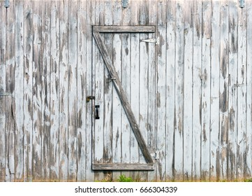 Rustic barn doors, wooden planks and locks closeup, peeling paint and weathered