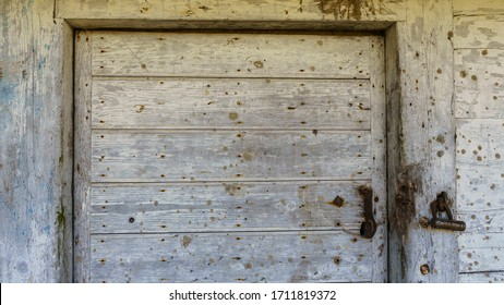 Rustic barn white door. Wooden planks and locks closeup. Peeling paint and weathered. Space for text. Texture and background.