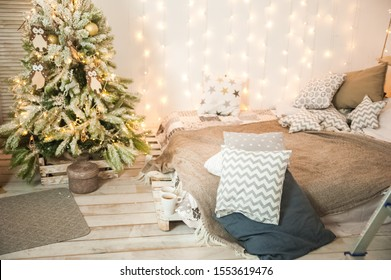 Rustic bedroom interior decorated for Christmas. New Year's interior Scandinavian style bed with pillows. Textural light room of a farmer's house with a Christmas tree and a garland. Background for te