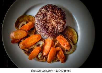 Rustic beef burger with potato carrots and onion garnish