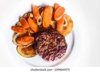 Rustic beef burger with potato carrots and onion garnish isolated on white background