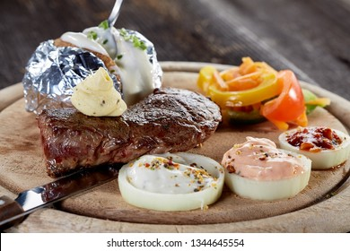 Rustic beef steak on old wooden board
