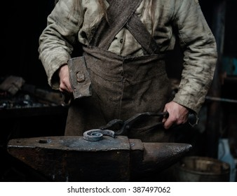 rustic blacksmith forges item on the anvil