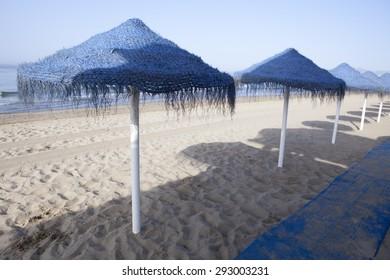 Rustic blue umbrellas made of natural fibers on a nice beach in Costa del Sol, Spain