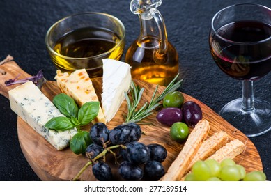 Rustic board with cheese selection,tapas style appetizer,grapes and herbs