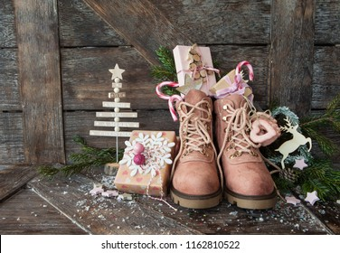 Rustic boots with christmas presents on wooden background