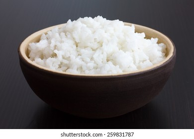 Rustic bowl of cooked white rice on dark surface.