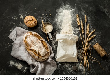 Rustic bread, flour sprinkled from the white paper bag, measuring cup and ears of wheat - kitchen. Captured from above (top view, flat lay) on black chalkboard background. Layout with free text space.