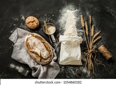 Rustikales Brot, Mehl aus dem weißen Papierbeutel, Messbecher und Weizenähren - Küche. Von oben (Draufsicht, flacher Hintergrund) auf schwarzem Chalkboard-Hintergrund erfunden. Layout mit freiem Textraum.