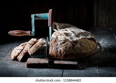 Rustic bread on slicer with flour and crumbs