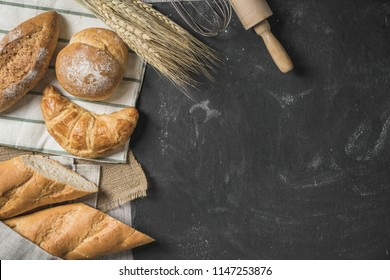 Rustic bread roll or french baguette, wheat and flour on black chalkboard. Rural kitchen or bakery - background with free text space.