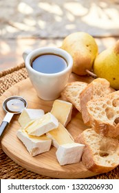 Rustic breakfast. Espresso and cheese plate. Brie, pears, walnuts, baguette bread