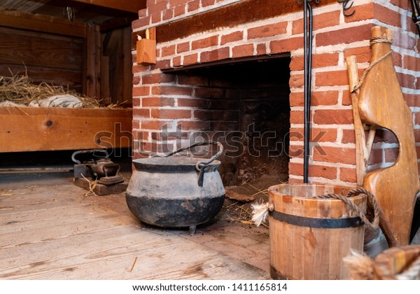 A rustic Brick Fireplace and huge Iron Kettle next to a straw bed and antique wooden bucket.