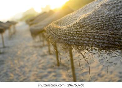 Rustic brown sun umbrellas made of natural fibers on a nice beach in Costa del Sol, Spain