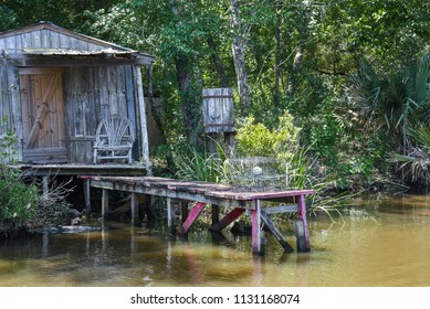 Rustic Cabin in the Bayou Swamp With Cistern, Traps, Wicker Chair and Red Dock