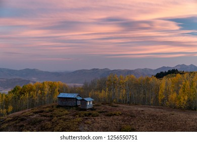 Rustic cabin on hill in Fall color during sunset