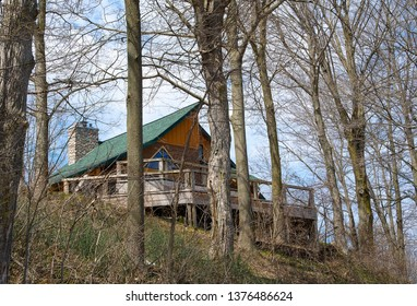 rustic cabin with wooden deck and green roof on a hill in spring woods