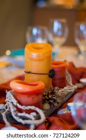 Rustic centerpiece with orange candles on wood plank