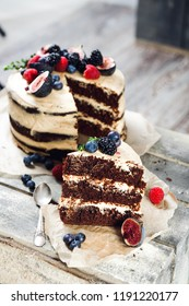 Rustic chocolate cake with one piece cut, lying on parchment paper