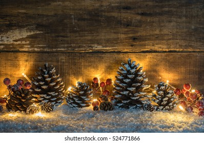 rustic christmas decoration snow pine cones red berries and shiny lights background - Rustic Christmas