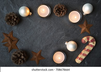 Rustic Christmas decorations and tea lights on dark stone surface with copy space in the center.  Viewed from directly above