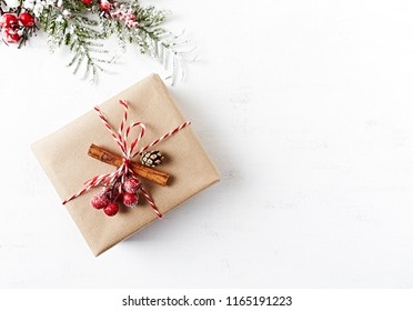 Rustic Christmas gift box with Christmas decorations on white wooden background. Flatlay. Copy space