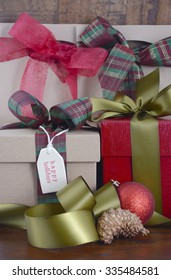 Rustic Christmas holiday gift in natural kraft paper gift box with Happy Holidays gift tag and traditional tartan ribbon on country style wood background.