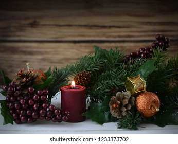 Rustic Christmas scene with pine, berries and a lit candle sitting on a white washed wooden table. Copy space. Vignette added.