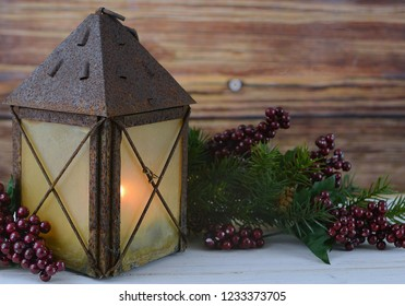 Rustic Christmas scene with pine, berries and a lit candle inside an old, rusty lantern on a whitewashed wooden table. Copy space.
