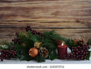 Rustic Christmas scene with pine, berries and a lit candle sitting on a white washed wooden table. Copy space.