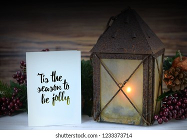 Rustic Christmas scene with pine, berries and a lit candle inside an old, rusty lantern on a whitewashed wooden table with vignette and a greeting message added.