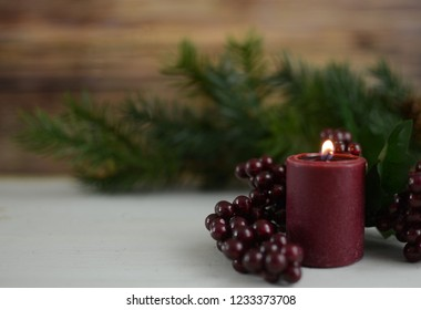 Rustic Christmas scene with pine, cranberry colored berries and a lit candle sitting on a white washed wooden table. Very shallow depth of field with focus on the candle flame. Copy space.