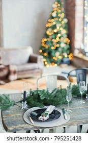 Rustic Christmas served table with vintage silverware, candles and fir twigs