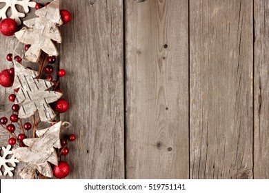 Rustic Christmas side border with wood ornaments and berries on an aged wood background
