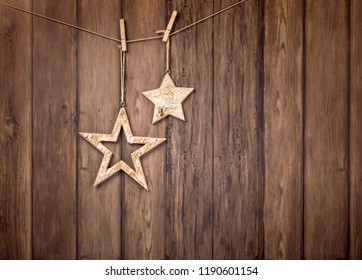 Rustic Christmas star decorations hanging with string on wood style backdrop