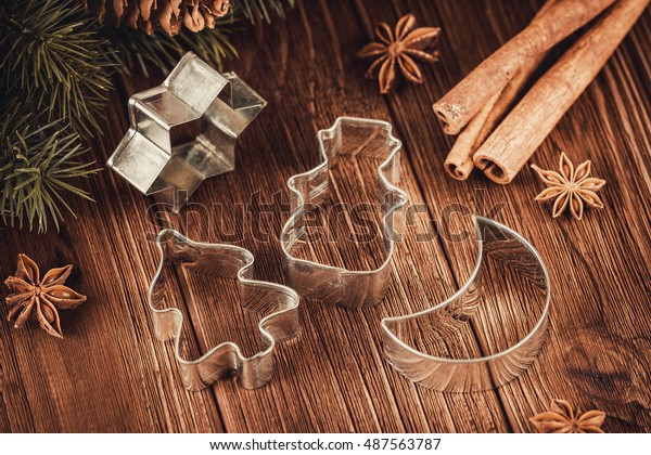 Rustic Christmas wooden background with cookies cutters, fir tree and cinnamon sticks. Shallow focus