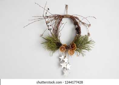 Rustic Christmas wreath with dried orange slices, pine cones and birch twigs. Frontal view on a gray concrete wall with copy space