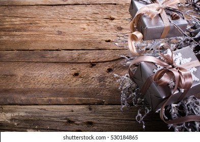Rustic Christmas wreath with gifts on wooden background. Free space for your text.