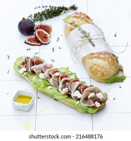 Rustic ciabatta sandwiches  with fresh figs ,ham, goat cheese, lettuce  with olive oil and springs of thyme on a white tiled countertop
