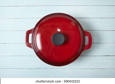 A rustic cooking pot on a blue wooden table top background