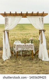 Rustic country chic vintage wooden wedding arbor arch with white curtains in an outdoor wedding aisle with a field of wheat in the background