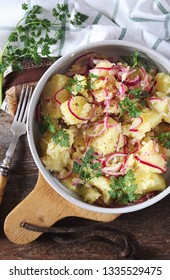 Rustic country potato salad with red onions and herbs. Top view