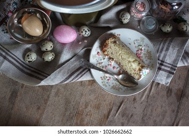 The rustic country still life of easter traditional food, top view.Painting and quail eggs, glass bottle,feud cloth,easter bread,spoon and plate on the wooden table.Shabby chic still life composition