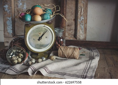 The rustic country still life of scale, old wood frames, painting and quail eggs, glass bottle with cinnamon sticks, feud cloth and bast on the wooden table. Shabby chic still life composition.