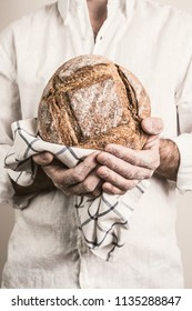 Rustic crusty loaf of bread in a strong baker man's hands - closeup. Small business and slow food concept. White background.