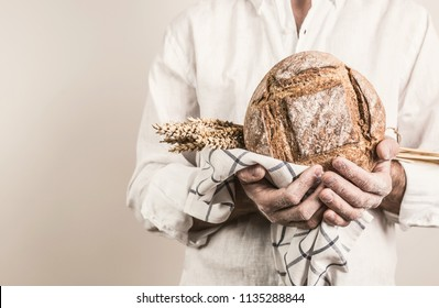 Rustic crusty loaf of bread and wheat in a strong baker man's hands - closeup. Small business and slow food concept. White background with free (copy) text space.